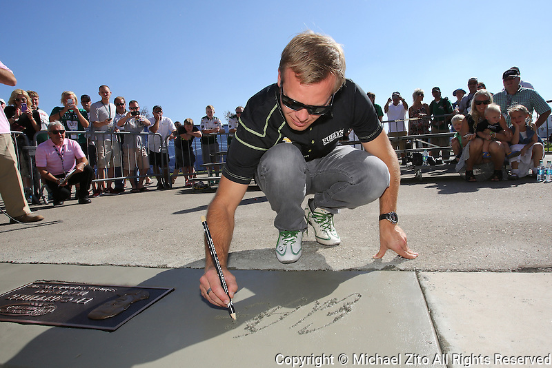 10/19/13 Fontana, CA: Ed Carpenter signs his name in wet cement at the Auto Club Speedway's walk of Fame before the MAVTV 500