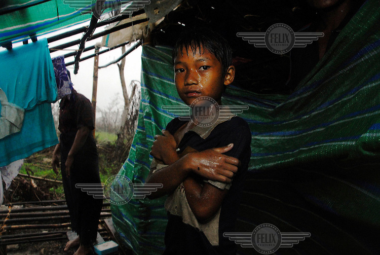 A family in a makeshift shelter on the road to Pyapon, offering little protection from the heavy monsoon rain. They lost their home when Cyclone Nargis hit Burma on 02/05/2008. Ayeyarwaddy Division.