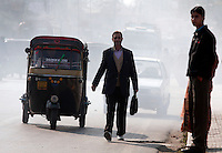 Man walking in traffic. Polluted street, being overtaken by auto rickshaw. Srinagar, Kashmir,India. © Fredrik Naumann/Felix Features