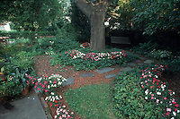 SHADE: Impatiens flowering in hidden planter boxes amid pachysandra under trees with flagstone walkway path