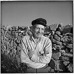 July 1996 -- Mykonos, Greek Islands -- A local villager on the island of Mykonos has a laugh in front of a rockwall wall..Andrew Kaufman©1996