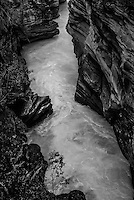 Black and white photo of water flowing through the gorge at Athabasca Falls in Jasper National Park Alberta Canada.