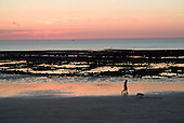 A couple walk their dog on the beach as the sun sets over the English Channel at the Normandy resort of Villierville.