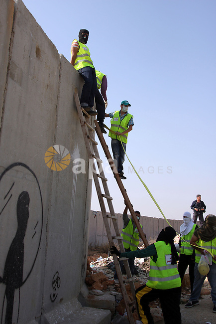 """Palestinian demonstrators prepare to pull down one segment of the concrete wall, part of the Israel's separation barrier,during a protest in the Qalandia refugee camp, near the West Bank city of Ramallah, on November 9, 2009 to mark the 20th anniversary of the fall of the Berlin Wall in Germany. Palestinians are using the anniversary of the end of the Berlin wall to press their campaign against Israel's """"wall"""", mostly a razor-wire fence interspersed with concrete barricades which Israel began building around the West Bank in 2002. The Jewish state has come under international censure for the barrier's de facto annexation of occupied West Bank land.. Photo by Issam Rimawi"""