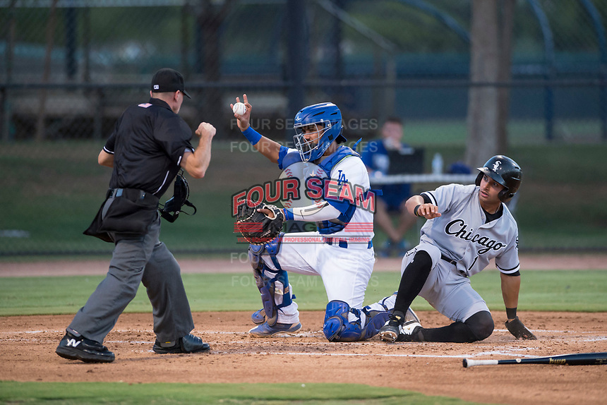 AZL Dodgers catcher Juan Zabala (54) shows the ball to home plate umpire Josh Williams after applying the tag to Camilo Quinteiro (1) during an Arizona League game against the AZL White Sox at Camelback Ranch on July 3, 2018 in Glendale, Arizona. The AZL Dodgers defeated the AZL White Sox by a score of 10-5. (Zachary Lucy/Four Seam Images)