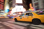 Panning shot of a yellow cab by night, Times Square, NYC, USA