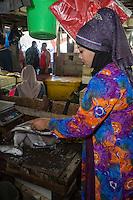 Bali, Indonesia.  Jimbaran Fish Market Vendor Preparing Fish for a Customer.