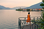 A woman in a yellow summer dress looks at the town of Gravedona, a town at the northern end of Lake Como, Italy at sunset