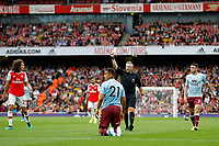 Anwar El Ghazi of Aston Villa is upended and referee, Jonathan Moss issues a yellow card during the Premier League match between Arsenal and Aston Villa at the Emirates Stadium, London, England on 22 September 2019. Photo by Carlton Myrie / PRiME Media Images.