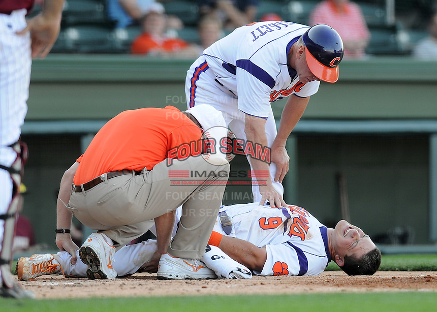 First baseman Phil Pohl (9) of the Clemson Tigers is attended to by head coach Jack Leggett and the team trainer after fouling a pitch off his leg in a game against the Elon College Phoenix on March 21, 2012, at Fluor Field at the West End in Greenville, South Carolina. Clemson won 4-2, giving head coach Jack Leggett his 1,200th win. (Tom Priddy/Four Seam Images)