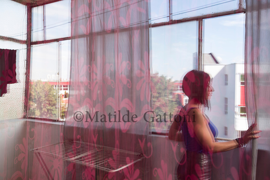 """Romania - Timisoara - Krina looks out from the window of her apartement. Krina, 25, is the longest-serving and the most representative camgirl at Live Cams Mansion. She joined the studio three years ago, after coming to Timisoara from her original village near the city of Constanta, in South-East Romania. Krina loves kickboxing, dreams of being a TV presenter and is currently trying to save enough money to set up her own business. """"Before I was working as a life insurer in a bank and it didn't feel good"""" she explains. """"Camming for me it's like acting, I like role plays.""""<br /> Krina sees herself as the """"psychologist"""" of her customers. """"Hearing their sad stories doesn't affect me right away, but I am sure it influences my subconscious and my life"""" she explains. On the other side, the job has helped her in becoming less judgemental and in reading people. """"I can quickly understand the type of client I have in front of me"""" she explains. """"It's all about taking control of the conversation, how you can communicate and how far you are willing to go."""""""