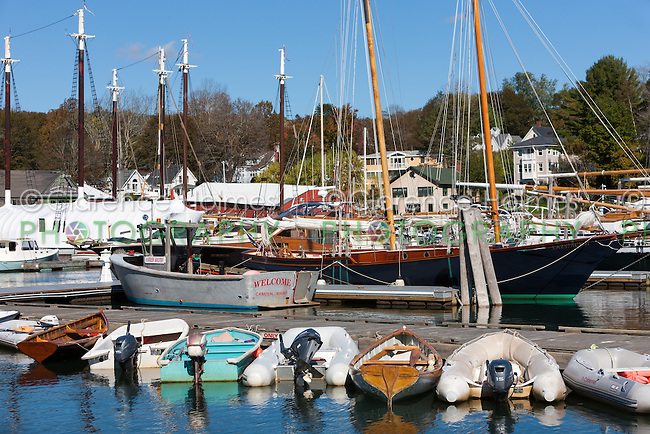 Dinghies line a dock in front of schooners and windjammers anchored in Camden harbor in Camden, Maine