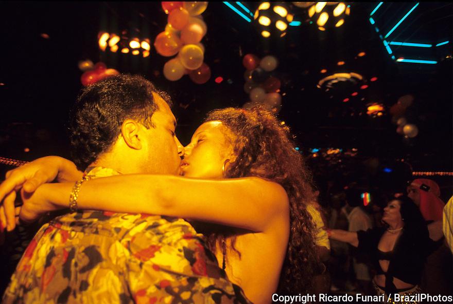 Young couple kissing and dancing in night club, Rio de Janeiro, Brazil.