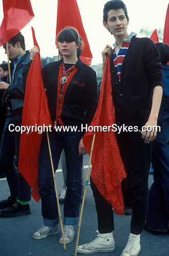 A young socalists couple holding red flags, gather  to hear speaches at the May Day rally in Hyde Park London England 1977.