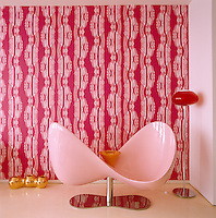 A pink curved loveseat desgined by Karim Rashid stands in front of a wall of the living room covered in a bold patterned wallpaper