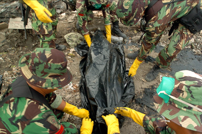 Indonesian Police pull a body from the mud in Bande Aceh, Indonesia. More than a week after the Asian Tsunami devastated the area, thousands of bodies have yet to be recovered. January 3, 2005. (James J. Lee for USA Today)