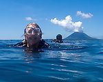 Nancy and another diver wait to be picked up by the dive boat in the waters of Bunaken National Park, off North Sulawesi, Indonesia.  The volcanic island Manado Tua is in the background.
