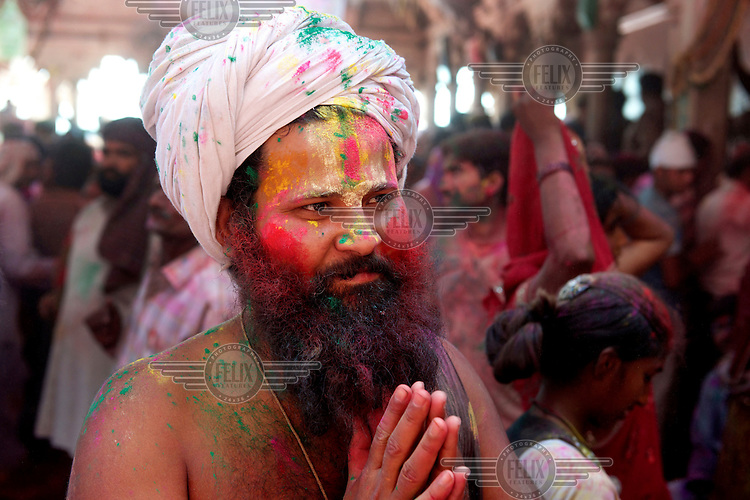 "A sadhu joins revellers gather at the Shriji Temple (Laadli Sarkar Mahal), during Lathmar Holi, smeared with coloured powder. It is held during a full moon and the town becomes swamped with tourists and revellers making the pilgrimage for a glimpse of ""God"", the Lord Shiva, who is revealed inside the temple only fleetingly."