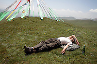 A man sleeps near to Tibetan prayer flags on top of a hill on the Qinghai-Tibetan Plateau, Qinghai Province. China. 2010