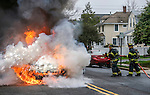 MANASQUAN, NJ — April 1, 2016 — A samll explosion happens as Manasquan firefighters Kevin McCredie and Tom Schofield squirt water on a 2000 Ford Focus that is fully engulfed in flames at about 9:40am on Broad Street, here. The driver of the vehicle, Nancy Trapani, was not injured.  photo by Andrew Mills