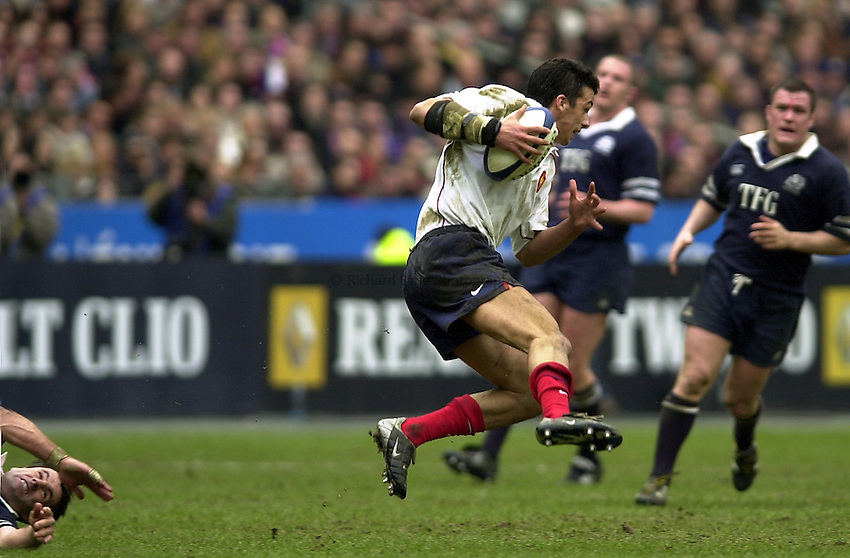 Photo Peter Spurrier.23/02/2003.Sport -SIX NATIONS RUGBY - France v Scotland.Clement Poitrenaud jumps over kenny Logan as he races across field