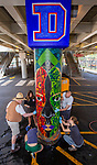 Brother Mark Elder, C.M., an adjunct faculty member in DePaul&rsquo;s art, media and design program, works with a group of current and former students, Saturday, July 28, 2018, as they install the second of three new murals under the Fullerton &quot;L&quot; Station in Lincoln Park. The colorful montage of historical images highlighting the 50th anniversary of DePaul's Black Student Union also remembers the student protests of 1969 held on campus. Other recent installations included a caricature of DePaul basketball star George Mikan, a 1959 Naismith Memorial Basketball Hall of Fame inductee, and a mural celebrating the opening of DePaul's Loop Campus.<br /> <br /> Elder's artistic retrospective, titled &ldquo;The Story of &lsquo;The Little School Under the &lsquo;L&rsquo;&rsquo;, will eventually feature 25 murals permanently installed on the massive concrete pillars that support the &quot;L&quot; station nearest the university's Lincoln Park Campus. (DePaul University/Jamie Moncrief)