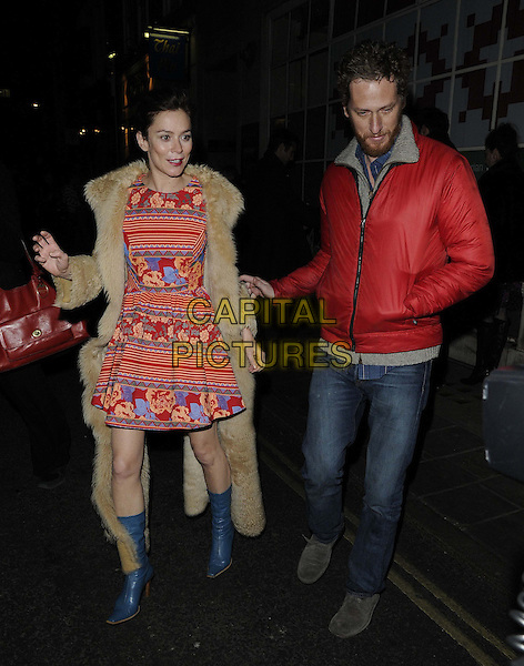 Anna Friel & guest.departed after the evening performance of 'Uncle Vanya', Vaudeville Theatre, The Strand, London, England..December 18th, 2012.full length beige fur coat red white yellow blue striped stripes floral print dress boots jacket jeans denim beard facial hair hand in pocket.CAP/CAN.©Can Nguyen/Capital Pictures.