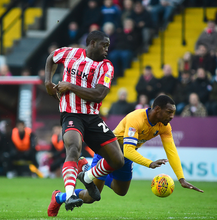 Lincoln City's John Akinde vies for possession with  Mansfield Town's Krystian Pearce<br /> <br /> Photographer Andrew Vaughan/CameraSport<br /> <br /> The EFL Sky Bet League Two - Lincoln City v Mansfield Town - Saturday 24th November 2018 - Sincil Bank - Lincoln<br /> <br /> World Copyright © 2018 CameraSport. All rights reserved. 43 Linden Ave. Countesthorpe. Leicester. England. LE8 5PG - Tel: +44 (0) 116 277 4147 - admin@camerasport.com - www.camerasport.com