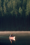 Glacier National Park, Woman kayaking on still lake, Bowman Lake, Montana, Rocky Mountains, USA, North America.