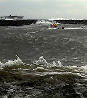 Thursday, Jan 21, 2010:  San Diego City Lifeguards drive a rescue boat in th Mission Bay Channel as high surf batters the jetty and OB Pier in the background.  WInter storms battered Southern California for a fourth day in a row, bringing strong wind, high surf and rain that caused flooding in many parts of San Diego.