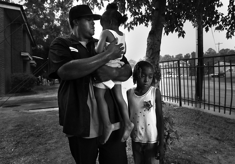 "AOF.FE.062907.EDR.JPG  Rodney Carolina (left), whose 15-year-old nephew Quincy Bowens died in his arms earlier that week, holds his 2-year-old daughter Zyandrea Carolina on Friday, June 29, 2007.  Quincy Bowens was ushering Zyandrea into her South Roxboro St. apartment in Durham when the drive-by shooting took his life.  Kamesha Alston (right), 9, was the oldest of four cousins who witnessed the killing. Rodney Carolina recalls Bowens' last moments, ""He was looking up at me with this expression in his eyes, like 'Help me. Help me.'  It was the first time in my life that I've felt helpless. I felt like losing it,"" said Carolina. ""I'm asking God to help me lift up my kids, to make me strong for them,"" he said.  ""I have faith that God will answer their questions. He will make a way for us.""   Staff photo by Ted Richardson/News & Observer..."