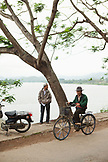 VIETNAM, Hue, a man rides his bike next to the Perfume River