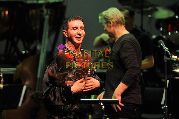 Marc Almond.performs 'Marc and the Mambas' Torment and Toreros, as part of the Meltdown Festival, Royal Festival Hall, Waterloo, London, England. .9th August 2012.on stage in concert live gig performance performing music half length flowers bouquet black shirt robe.CAP/MAR.© Martin Harris/Capital Pictures.