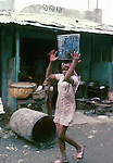Woman carrying can of water on her head. Images of the capital,Port au Prince, Haiti 1975