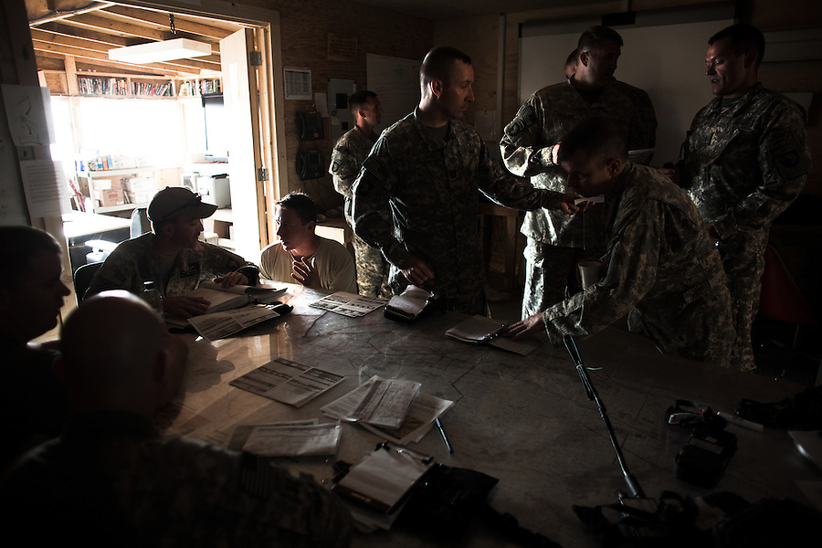 "Pilots go through a briefing prior to heading out on mission. The pilots of Charlie and Bravo Troops 2nd Squadron 17th Cavalry Regiment - part of the 101sst Airborne Division - fly missions over the critically contested landscape of Kandahar in their OH-58 Kiowa Warrior scout-attack helicopters. Thinking of themselves as the ""infantry of the sky,"" 2/17 CAV's mission is to fly low and fast over the battlefield relaying reconnaissance information to ground-bound troops - scanning for the enemy, looking for signs of IED placement, reporting on the movements and activities of civilians - and bringing their ship's rockets and machine-guns to bear on enemy fighters when they can be found.."