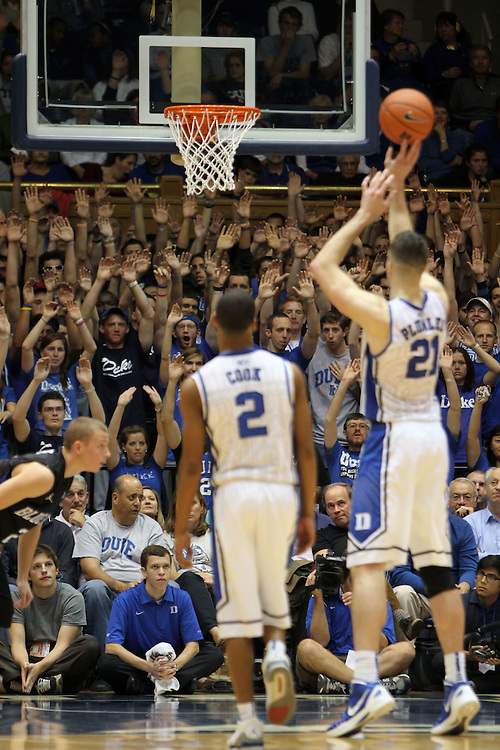 Duke fans hold up thier arms as Miles Plumlee shoots a foul shot. Duke beat Presbyterian 96-55 on Saturday, November 12, 2011 at Cameron Indoor Stadium in Durham, NC. It was win number 902 for Duke head coach Mike Krzyzewski, tying him with Bob Knight for the NCAA Division I all-time win record. Photo by Al Drago.