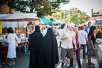 "Islamic women in full burqas walk through the Brighton Beach Jubilee in the Brighton Beach neighborhood of Brooklyn in New York on Sunday, August 25, 2013. The neighborhood is sometimes colloquially named ""Little Odessa"" because of its popularity amongst Russian emigres and its proximity to the ocean. (© Richard B. Levine)"