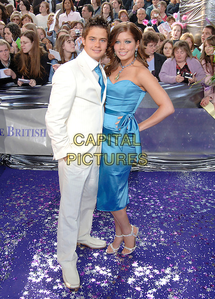 DANNY YOUNG & NIKKI SANDERSON.British Soap Awards, BBC Television Centre, London, .May 7th 2005..full length couple blue satin Kyri dress bow sash strapless cream suit hand in pocket on hip nicki nicky.Ref: PL.www.capitalpictures.com.sales@capitalpictures.com.©Capital Pictures