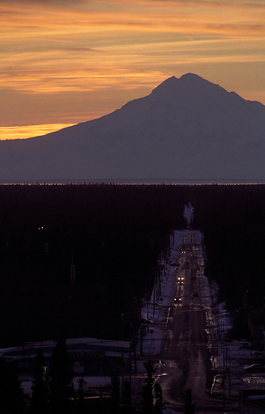 Mount Redoubt looms above traffic moving on Marydale Avenue in Soldotna, Alaska. The 10,197-foot tall volcano is across Cook Inlet, about 50 miles from the sister cities of Soldotna and Kenai.