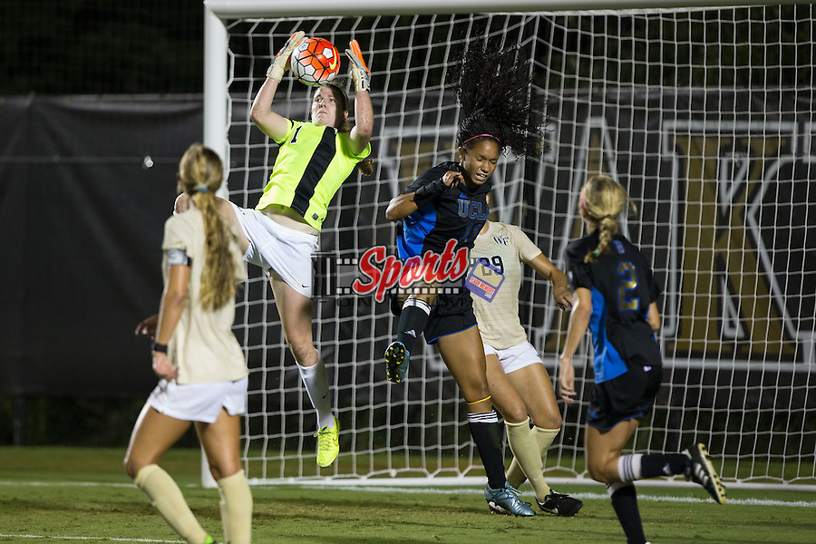 Lindsay Preston (1) of the Wake Forest Demon Deacons makes a save in front of Darian Jenkins (11) of the UCLA Bruins during second half action at Spry Soccer Stadium on September 11, 2015 in Winston-Salem, North Carolina.  The Bruins defeated the Demon Deacons 2-1.  (Brian Westerholt/Sports On Film)