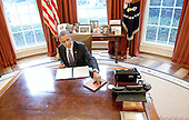 """United States President Barack Obama signs a presidential memorandum """"Modernizing Federal Leave Policies for Childbirth, Adoption, and Foster Care to Recruit and Retain Talent and Improve Productivity"""" for federal employees in the Oval Office of the White House in Washington, DC, January 15, 2015. <br /> Credit: Olivier Douliery / Pool via CNP"""