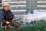 A cowboy firing a rifle
