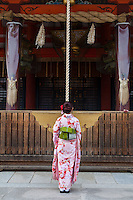 A woman in a kimono prays at Yasaka Shrine, also known as Gion Shrine, in Gion, Kyoto, Japan. Sunday April 24th 2016