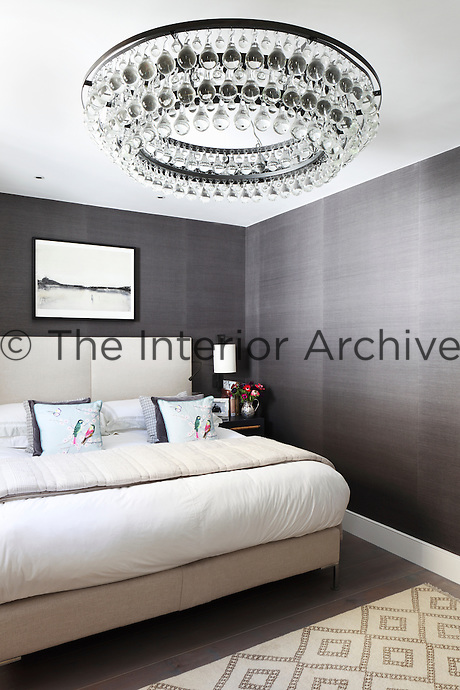 An eye-catching chandelier of glass baubles hangs from the ceiling of this contemporary bedroom designed by Turner Pocock