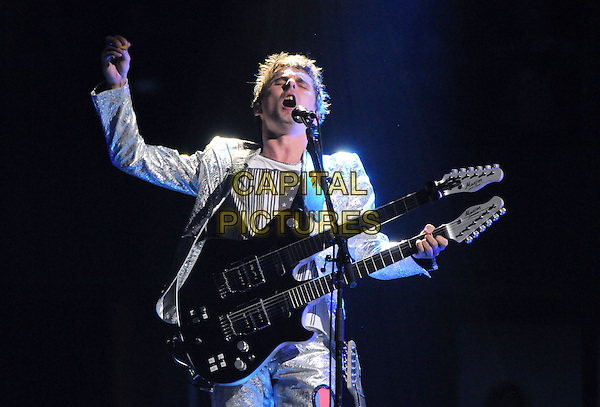 "MATT BELLAMY of MUSE.Muse perform live at Honda Center during their ""Resistance Tour 2010"" in Anaheim, California, USA, .September 23rd 2010..music concert gig live on stage half length singing silver jacket shiny suit guitar microphone  playing arm   Matthew                                             .CAP/RKE/DVS.©DVS/RockinExposures/Capital Pictures."