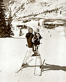 USA, Utah, mother and daughter skiing towards the mountain base, Alta Ski Resort (B&W)
