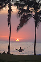 Woman relaxing in hammock at sunset in front of ocean, Alii Beach Park, Haleiwa, North shore of Oahu, Hawaii