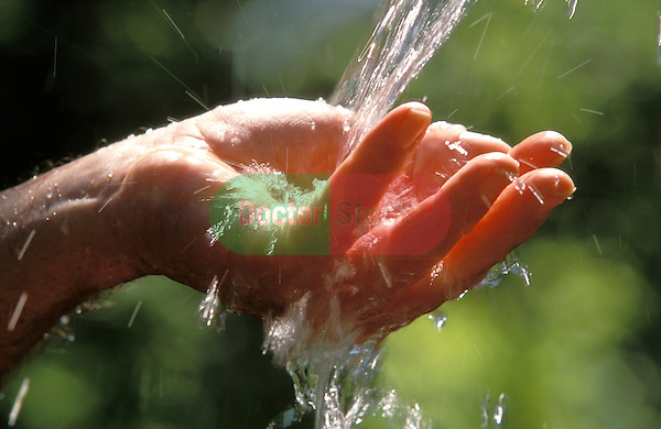 Man's hand catching flow of fresh water