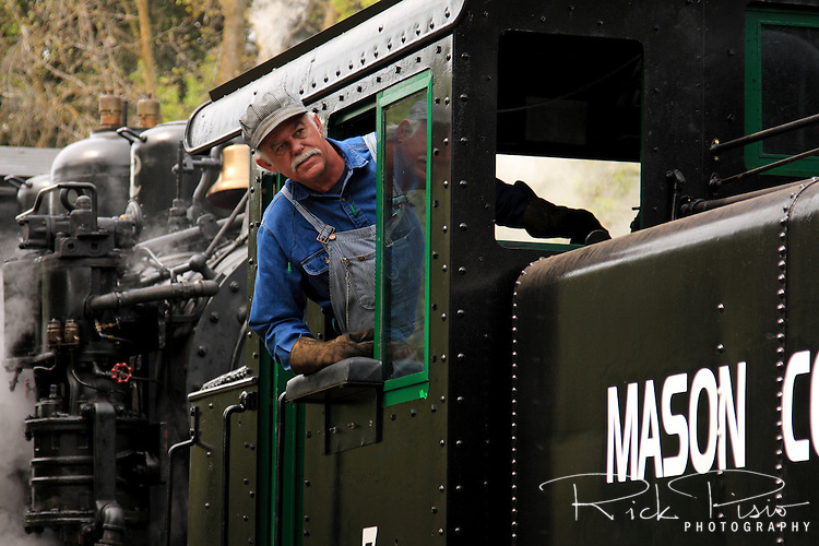 The engineer leans out of the cab of the steam locomotive Mason County Logging #7. he Mason County Logging Co. #7 was built in 1910 by the Baldwin Locomotive Works.