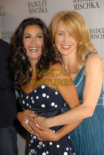 TERI HATCHER & FELICITY HUFFMAN.The New Badgley Mischka Campaign, held at One Sunset Restaurant in West Hollywood, California, USA. .August 27th 2007.half length teal top camisole blue and white strapless polka dot dress funny arms black hug embrace .CAP/ADM/BP.©Byron Purvis/AdMedia/Capital Pictures